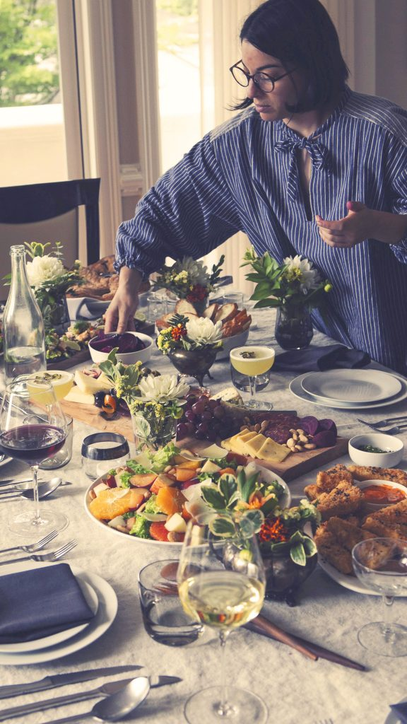 Photograph of Woman Placing Food on Table